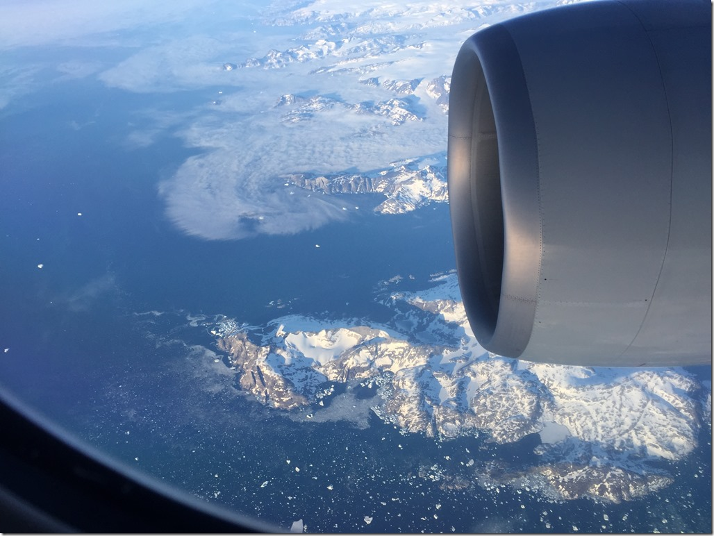 Picture from airplane of Greenland showing snow-covered landscape and surrounding ocean with iceburgs